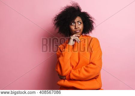 Perplexed african american woman posing and looking aside isolated over pink background