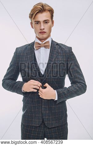 Handsome young man with blond hair poses in elegant classic suit and a bow-tie in white luxury apartments. Men's beauty, fashion.
