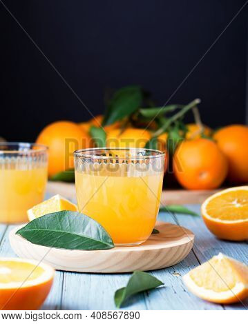 Two Glasses Of Fresh Juice, Fruit Squeezer And Ripe Fresh Oranges On Blue Wooden Table Top, Fresh Or
