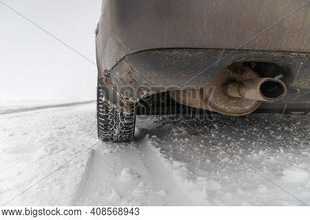 Close-up Of The Exhaust Pipe, The Rear Wheel Of The Car In The Snow On The Side Of The Road. Copy Sp