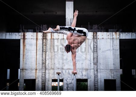 Flexible Male Circus Artist Keep Balance By One Hand In The Concrete Structure. Confidence And Aspir