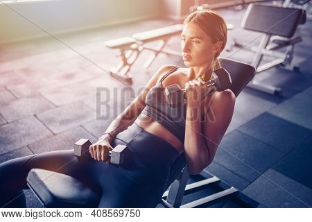 Fit Woman Workout With Dumbbells Doing Exercise For Biceps Muscle In Gym.
