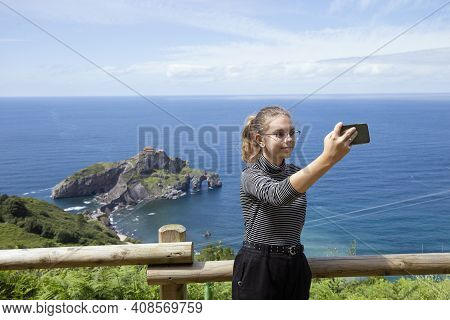 Close-up Shot Of Lovely Young Girl Taking Selfie At Bay Of Biscay, Spain.