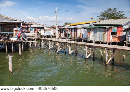 Coastal View Of The Poor District Of Kota Kinabalu City, Malaysia. Small Living Houses And Footbridg