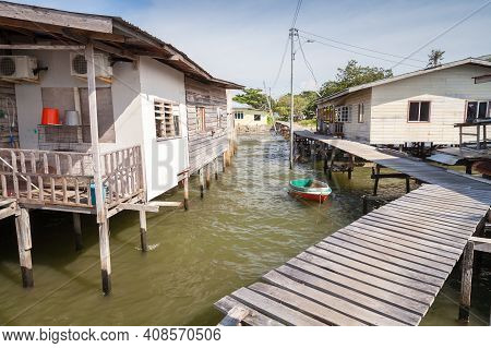 Street View Of The Poor District Of Kota Kinabalu, Sabah, Malaysia. Old Wooden Houses And Footbridge