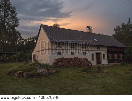 Sunset View Of Half Timbered Masonry, Old Rustic Cottage House With Chopped Wood In Summer Garden Wi