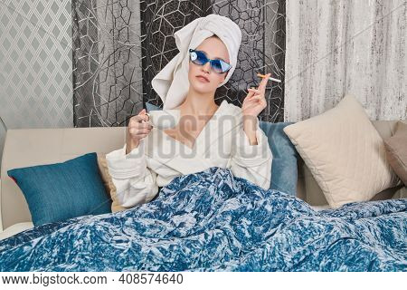 Glamorous young woman with elegant blue sunglasses, a white bathrobe and with a towel around her hair after a shower lies in her cozy bed, drinks coffee and smokes a cigarette. Luxurious lifestyle.
