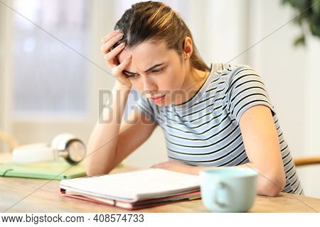 Frustrated Student Studying Complicated Lesson Reading Notes On Notebook At Home
