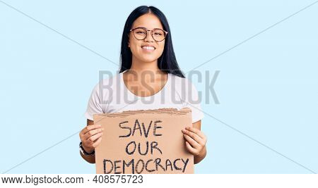 Young beautiful asian girl holding save our democracy protest banner looking positive and happy standing and smiling with a confident smile showing teeth