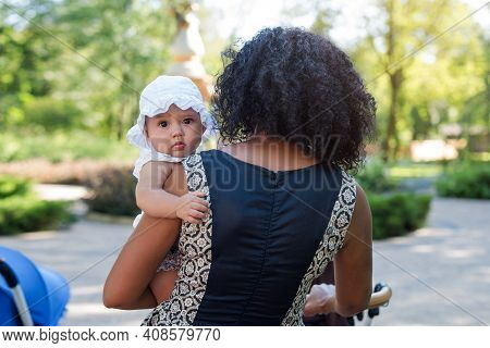 Young African American Woman And Her Daughter Walking In Summer Park. Black Mother Playing With Her