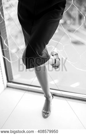 Woman In Medium-length Dress And High-heeled Shoes Stands At The Window, Her Heel Resting On The Gla