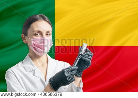 Girl Doctor Prepares Vaccination Against The Background Of The Benin Flag. Vaccination Concept Benin