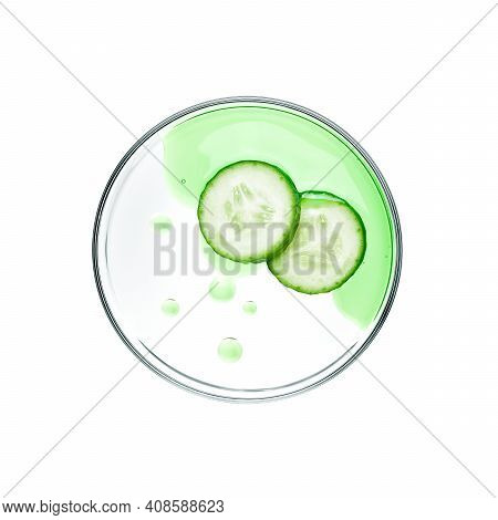 Sliced Cucumbers With Essence On Petri Dish Over White Background