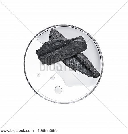 Black Charcoal With Essence On Petri Dish Over White Background