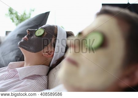 Man And A Woman Are Lying On Couch With Rejuvenating Mask On Their Face. Home Treatments For Facial