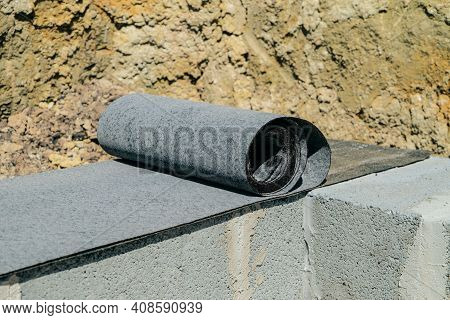 Waterproofing The Basement Of A House Under Construction. Rolled Bitumen Waterproofing Material In T