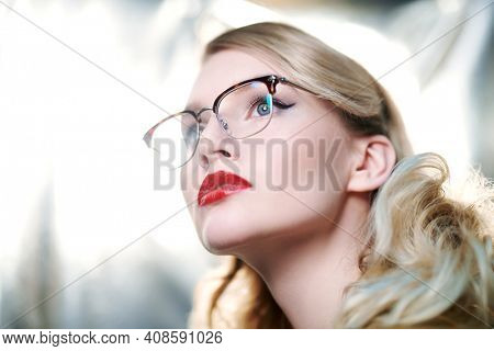 Portrait of a beautiful young woman in modern glasses. Optics and eyewear style.