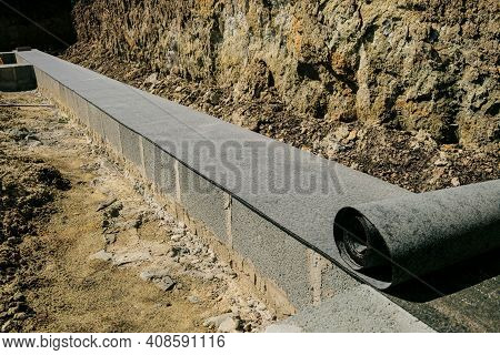 Long Line Of Rolled Bitumen Waterproofing Material In Two Layers Lies On The Masonry Of Concrete Blo