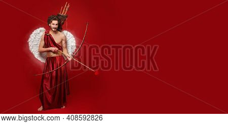 Full length portrait of a Cupid with the bow and arrow of love on a red background. Copy space. Valentine's Day concept.