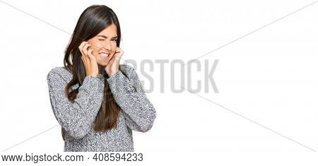 Young brunette woman wearing casual winter sweater covering ears with fingers with annoyed expression for the noise of loud music. deaf concept.