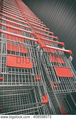 Shopping Metallic Cart Lined Up In Rows In The Shop Parking. Supermarket Aisle With Empty Red Shoppi