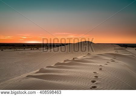 Footsteps In The Sand Of A Dune In The Mungo National Park Desert Just As The Sunset