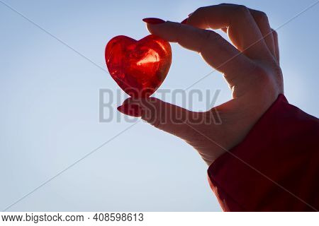 Heart In Hand. Red Heart In A Woman's Hand, On A Light Background Close-up. The Concept Of Love, Fri