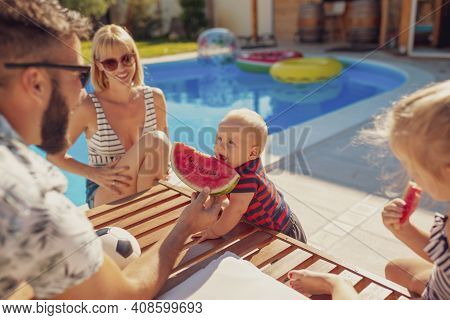 Parents Having Fun Spending Hot Sunny Summer Day By The Swimming Pool With Their Children, Father Fe