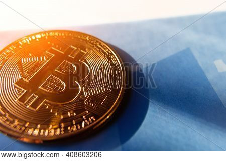 Bitcoin Coin On A Blue Background With A Glare Of The Sun.
