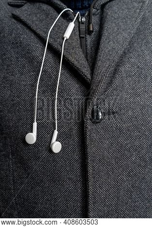 White Headphones On The Background Of A Man's Coat Close Up.