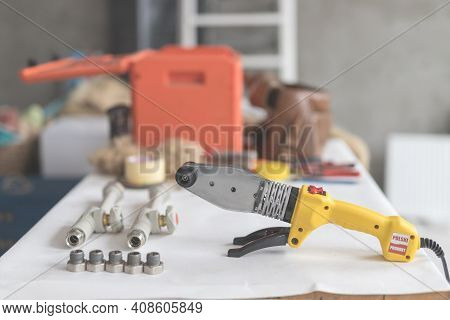 Soldering Iron For Polypropylene On White Table. Side View Of Yellow Iron For Heating Or Water Suppl