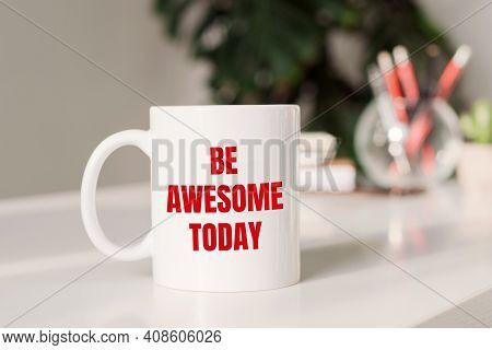 Coffee Mug With Text Be Awesome Today In Workplace Background.