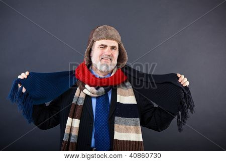 Smiling business man trying on a hat and scarf