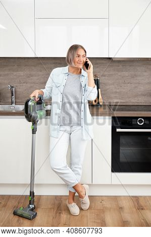Young Woman Vacuuming The Floor. Vacuuming And Cleaning The House