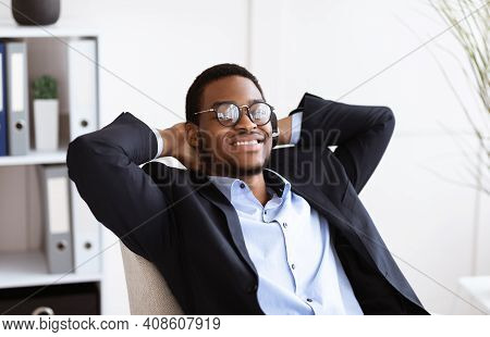 Joyful Black Businessman In Suit Reclining On Chair And Smiling In His Modern Office, Having Break A