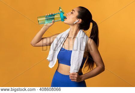 Fitness And Healthy Lifestyle Concept. Portrait Of Sporty Young Woman Drinking Mineral Water From Bo