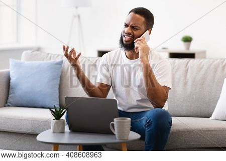 Discontented Black Guy Talking On Cellphone Sitting At Laptop Having Computer Problem At Home. Displ