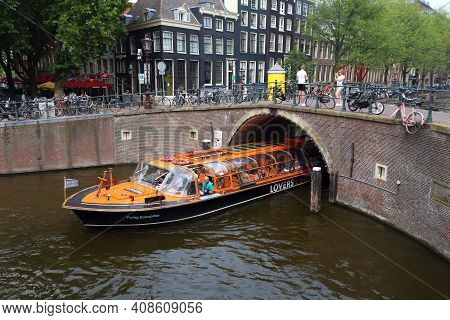 Amsterdam, Netherlands - July 10, 2017: People Ride A Tour Boat At Herengracht Canal In Amsterdam Ci