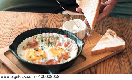 Man Spreading Butter On The Bread With Pan Fried Egg With Toppings