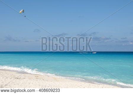 Parasailing On The Tropical Sea Near An Exotic Beach In Cancun, Mexico. Summer Fun And Recreation Ac