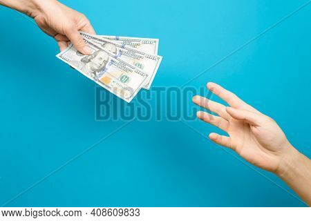 Female Hand Giving One Hundred Dollar Bills And Male Hand Reaching For Money, Blue Background. Conce