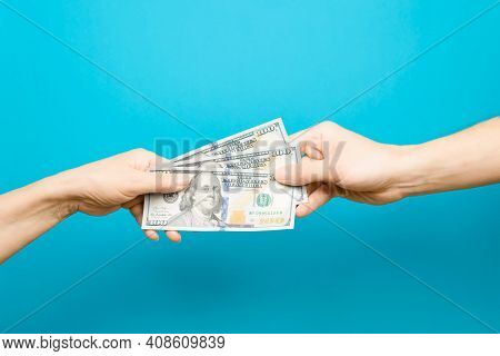 Hand Giving One Hundred Dollar Bills And Hand Taking Money, Blue Background. The Concept Of Salary,