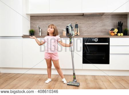 Little Girl Using Vacuum Cleaner In Room. Vacuuming And Cleaning The House. Housework