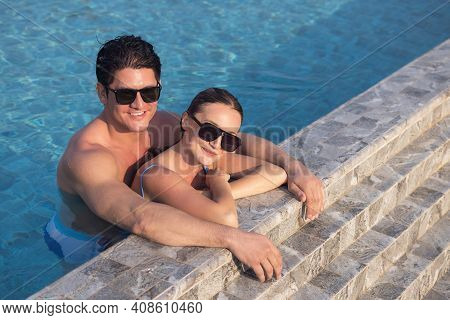 Very Happy Couple Wearing Sunglass Enjoy Each Other In Swimming Pool. Man Holding Woman On Hands