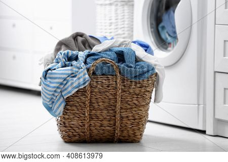 Wicker Basket With Dirty Laundry On Floor Indoors