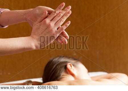 Masseuse Preparing For Doing Aromatherapy Oil Massage In Spa Salon. Close-up Of The Hands Of A Masse