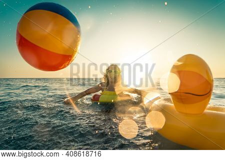 Happy Child Having Fun On Summer Vacation. Kid Playing With Rubber Duck And Ball In The Sea. Healthy