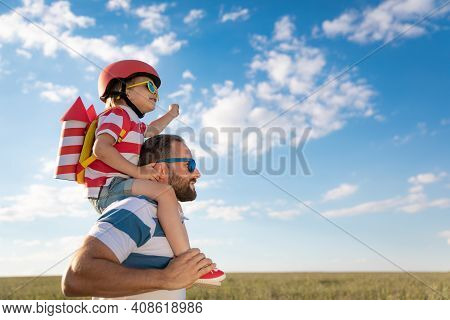 Happy Family Having Fun Outdoor. Father And Son Playing Against Blue Summer Sky Background. Imaginat