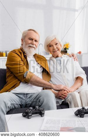Kyiv, Ukraine - December 17, 2020: Smiling Elderly Couple Hugging On Couch Near Gamepads And Newspap