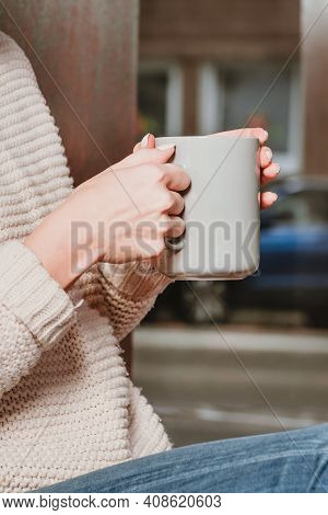 Beautiful Woman Holding A Cup Of Coffee In Her Hands. In A Knitted Beige Sweater.a Girl In A Beige S